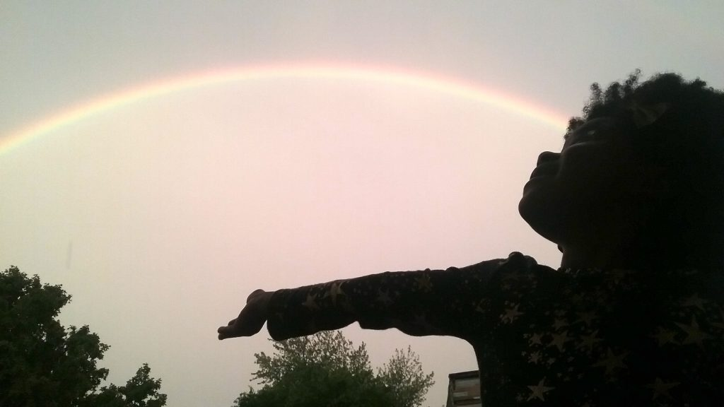 A little girl standing under a rainbow
