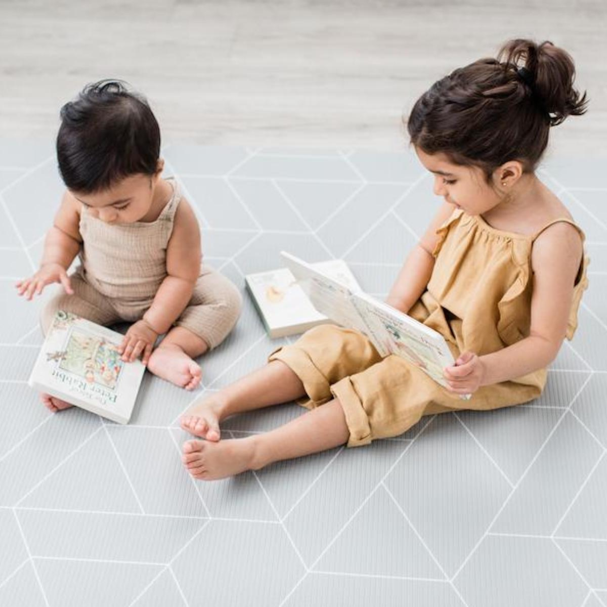 A little girl and an infant reading two books on a Little Bots playmat