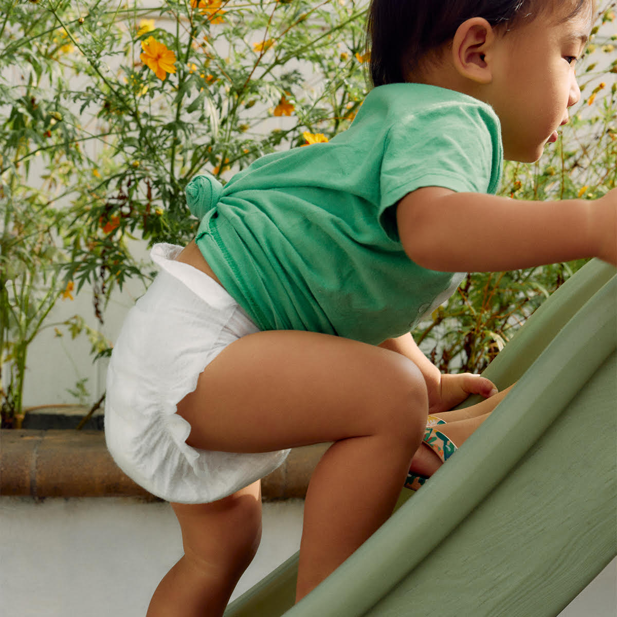 A baby wearing a green shirt and a Coterie diaper