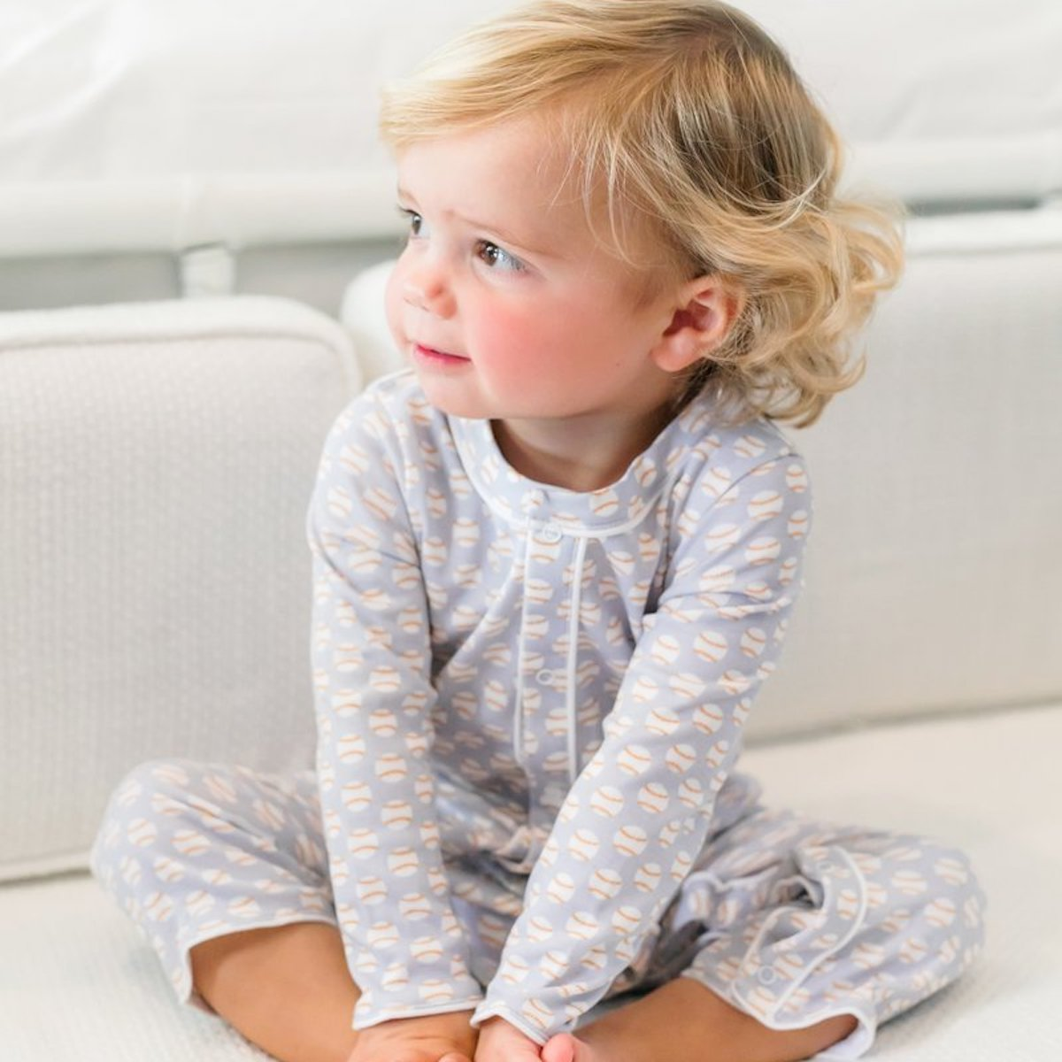 A blonde baby sitting cross-legged wearing Lila and Hayes pajamas