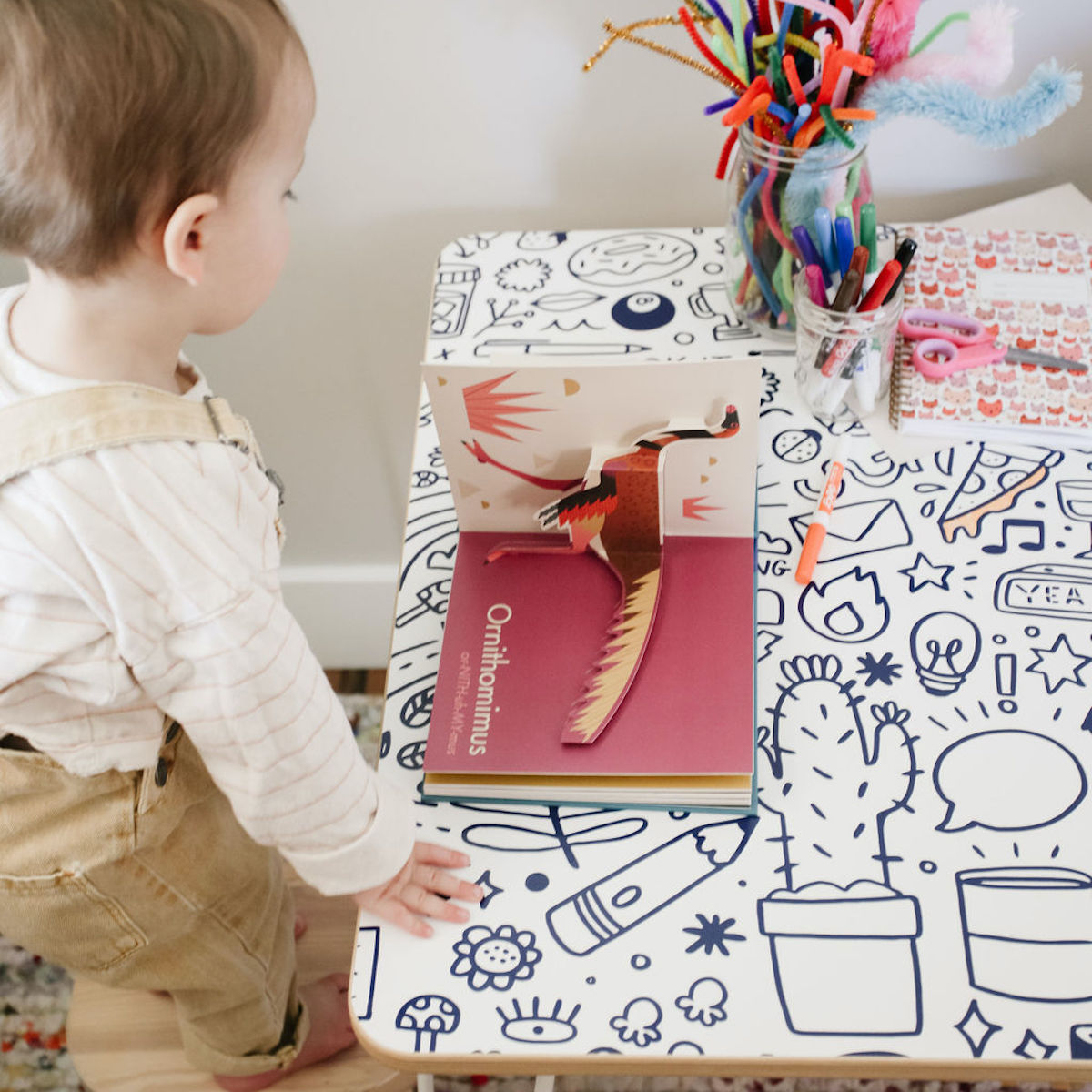 A little boy reading a book on a Chassie brand table