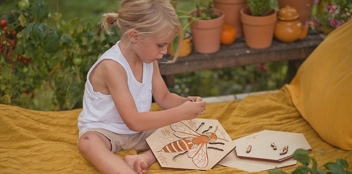 A child playing with the Stuka Puka Bee Anatomy Wooden Puzzle