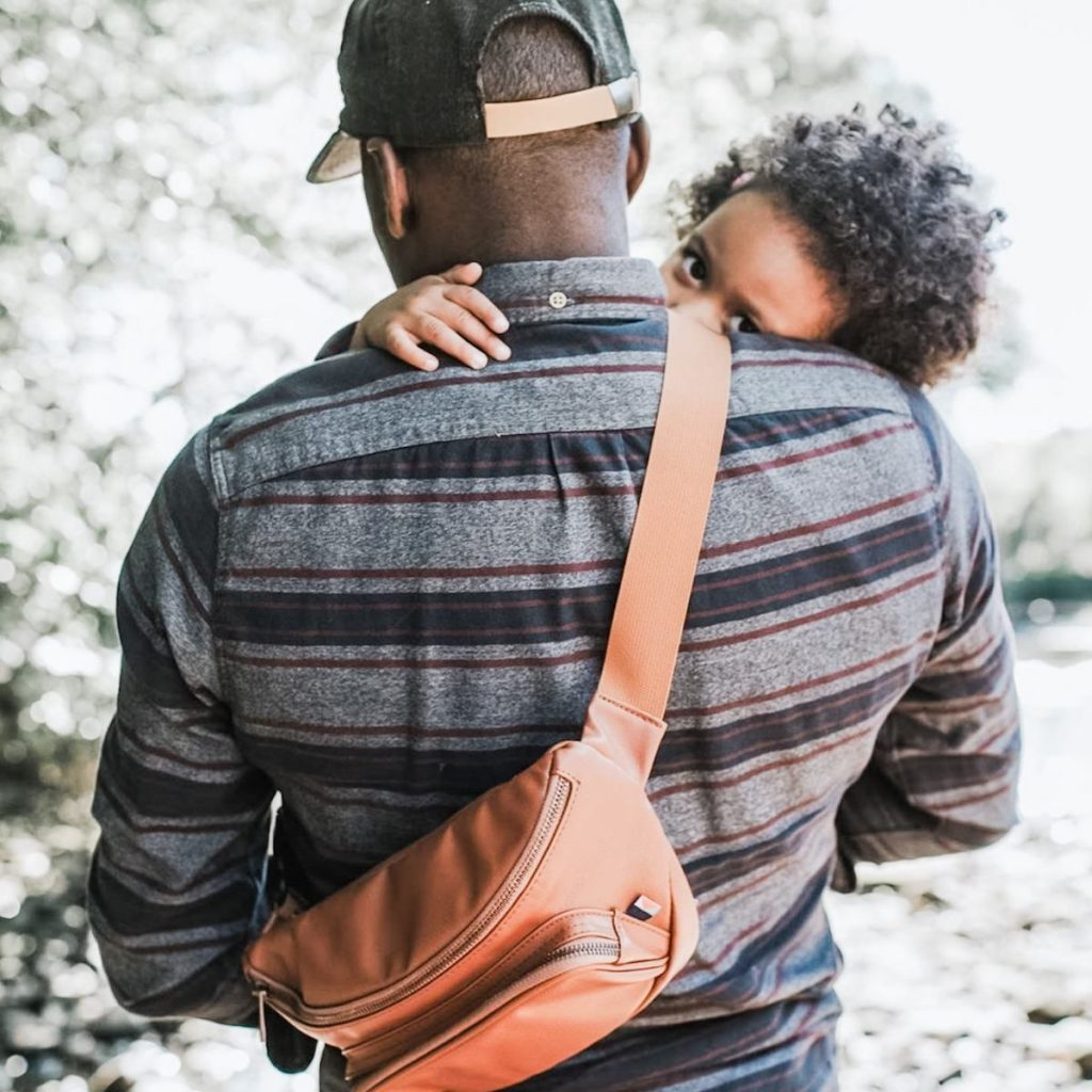 A father wearing a baseball cap and a Kibou diaper bag holding his child while going for a walk outdoors