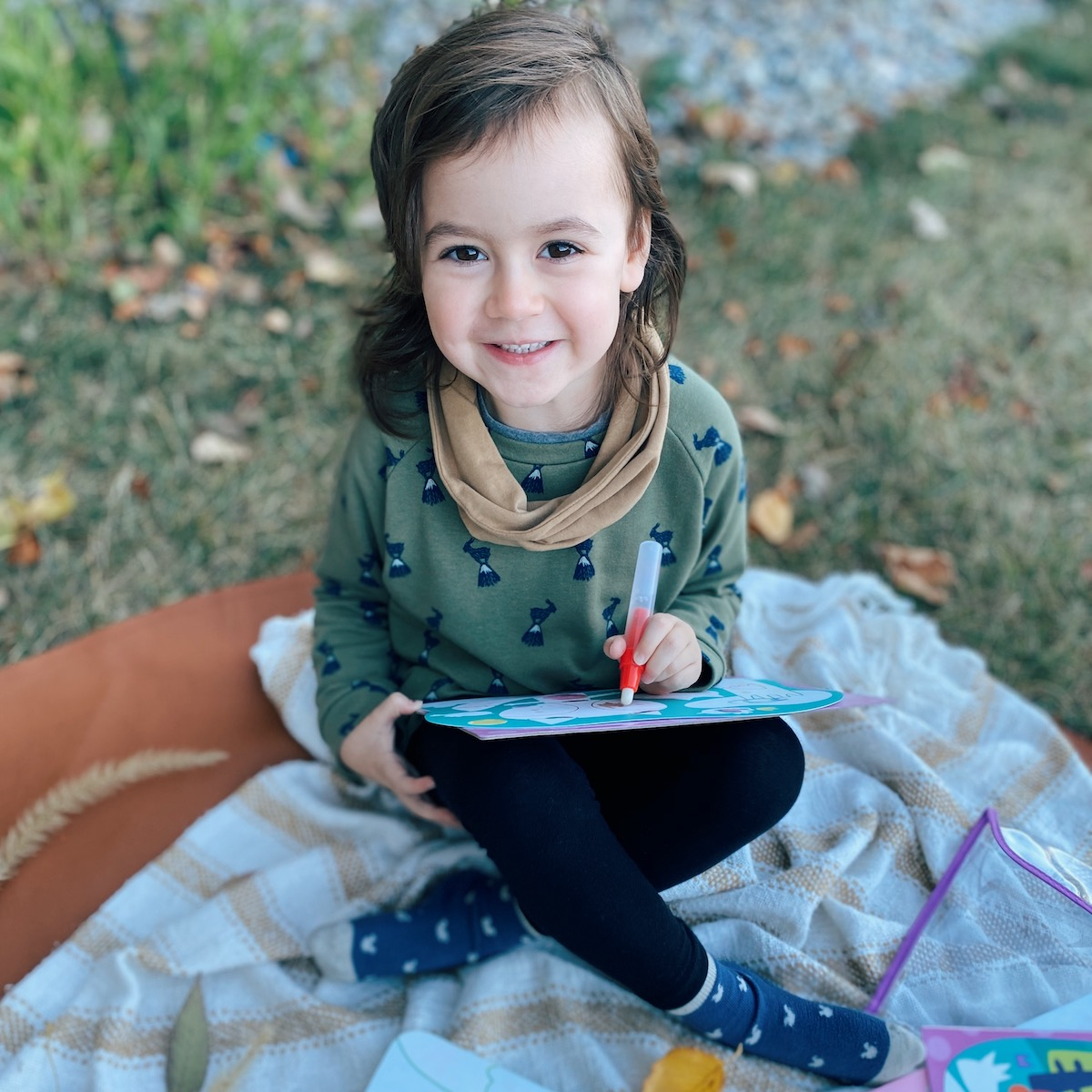 A little girl sitting on a picnic blanket outdoors coloring with a Djeco coloring book