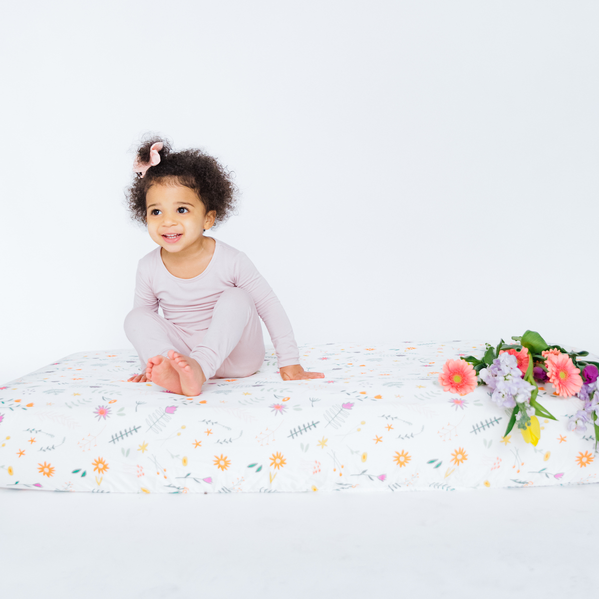 A toddler wearing pajamas and sitting on a Field of Dreams Crib Sheet by Coco Bean with a bunch of flowers