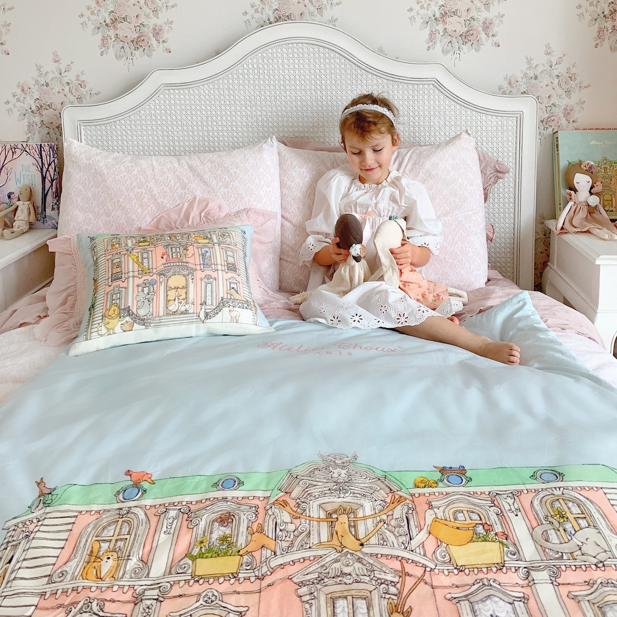 A little girl holding a doll and sitting on her bed with an Atelier Choux bedding set