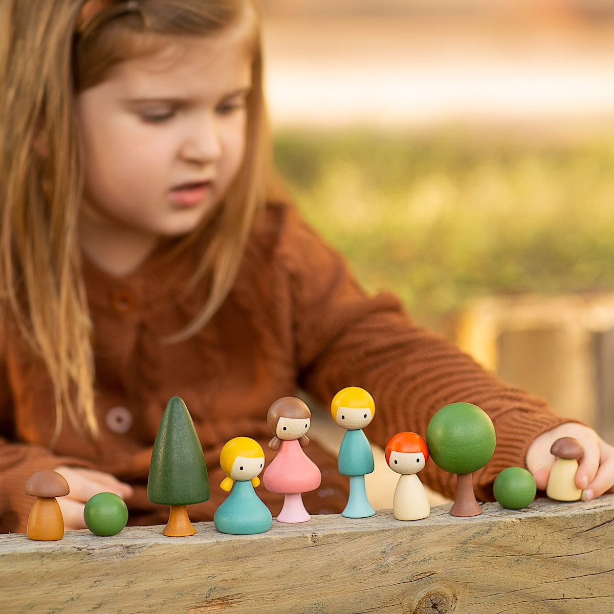 A little girl sitting at a picnic table outdoors playing with Clicques wooden dolls