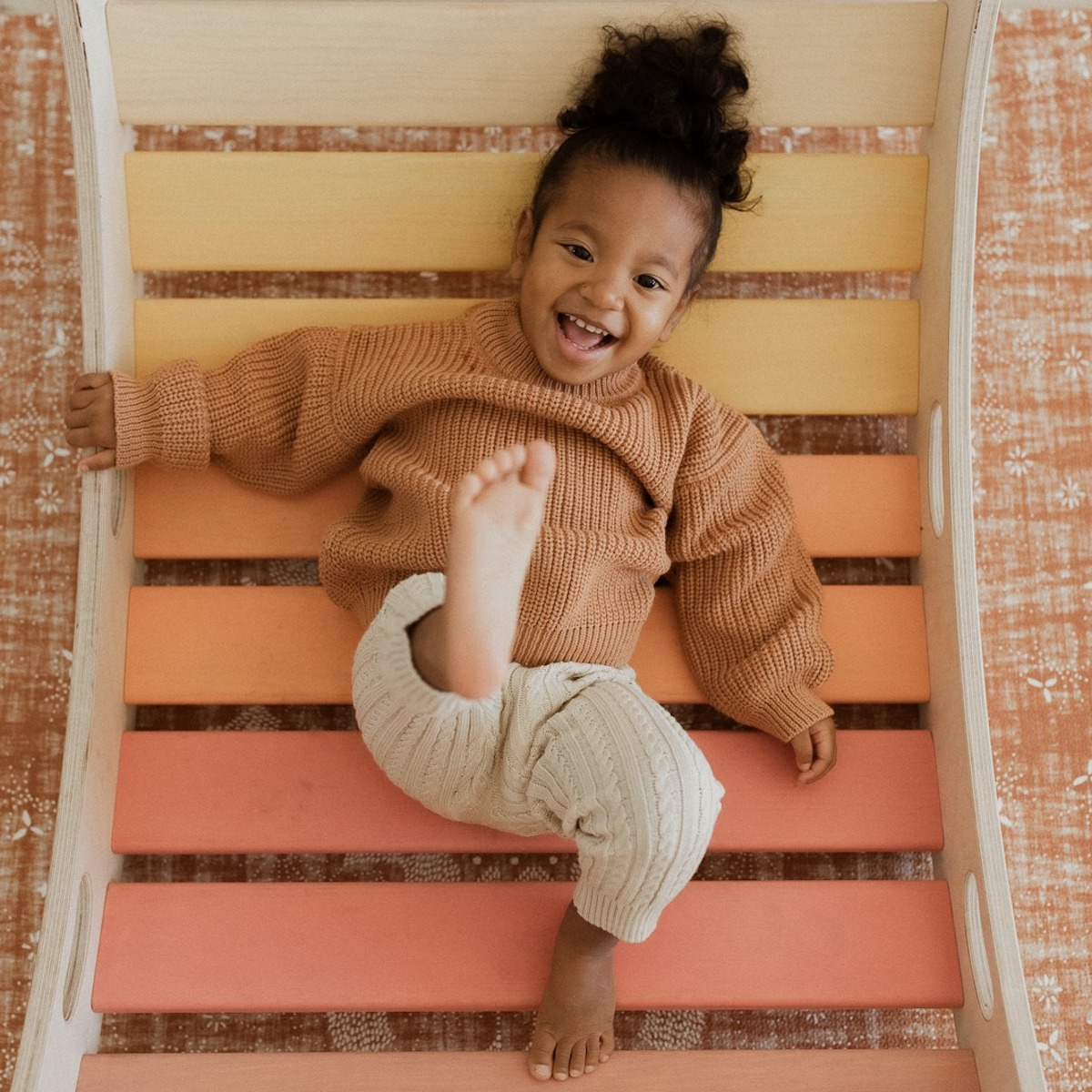 A little girl wearing a brown sweater and lying on a Wiwiurka climbing frame
