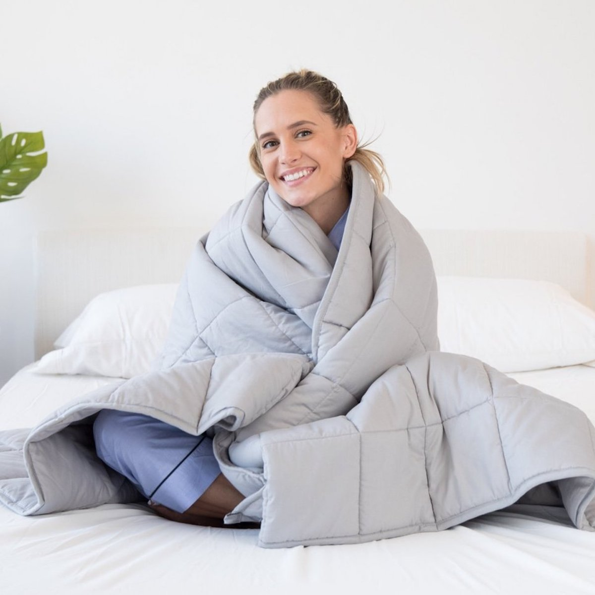 A woman sitting on her bed wearing a Luna weighted blanket