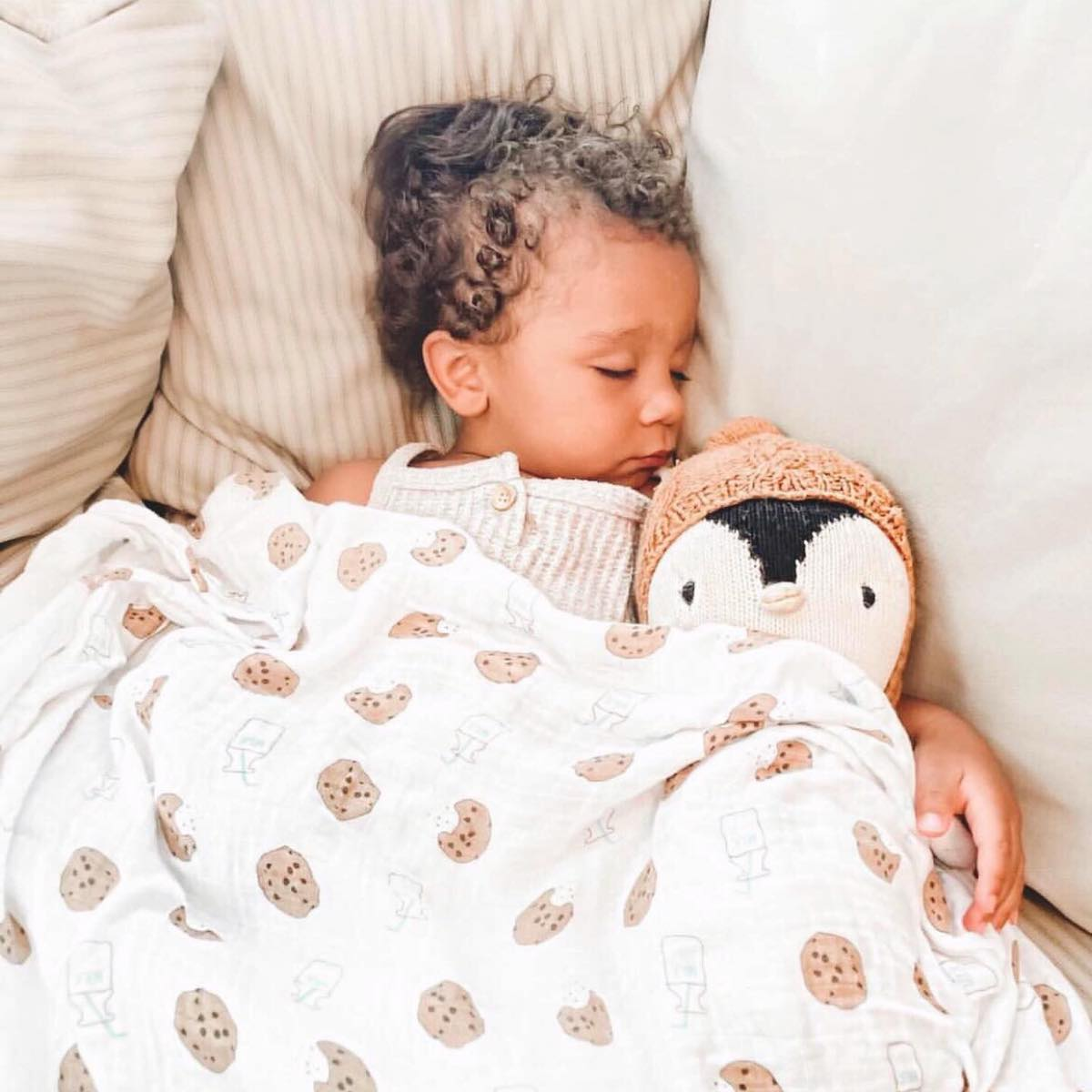 A toddler sleeping in a bed with a penguin stuffed animal with a Bundled Baby swaddle