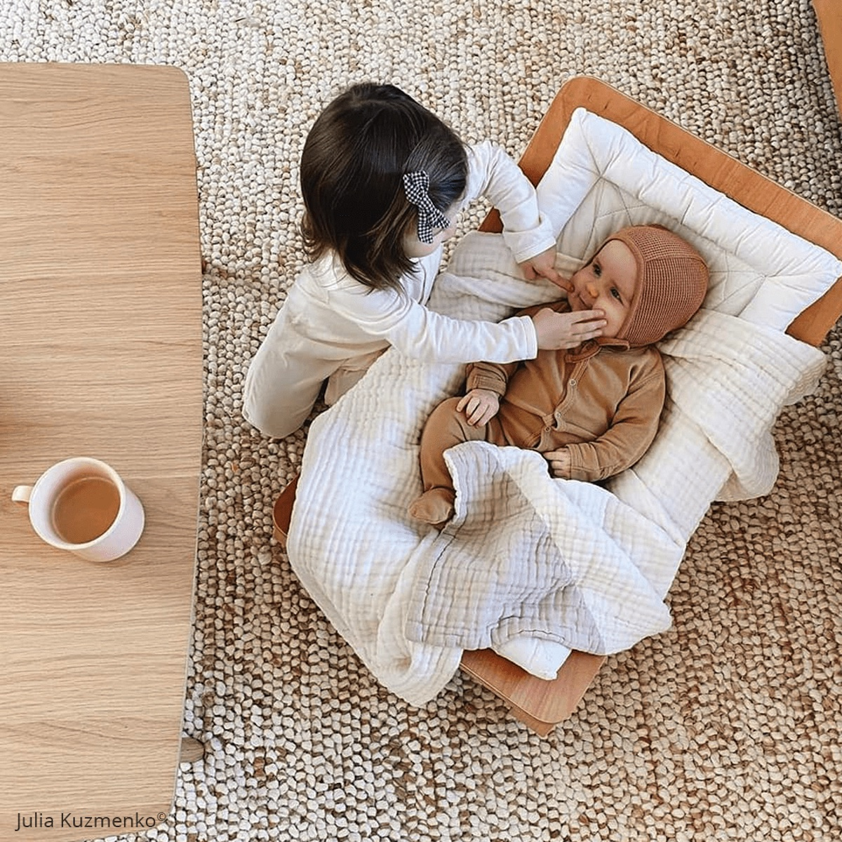 A young girl tending to her infant sibling in a Charlie Crane rocker next to a coffee table with a cup of tea