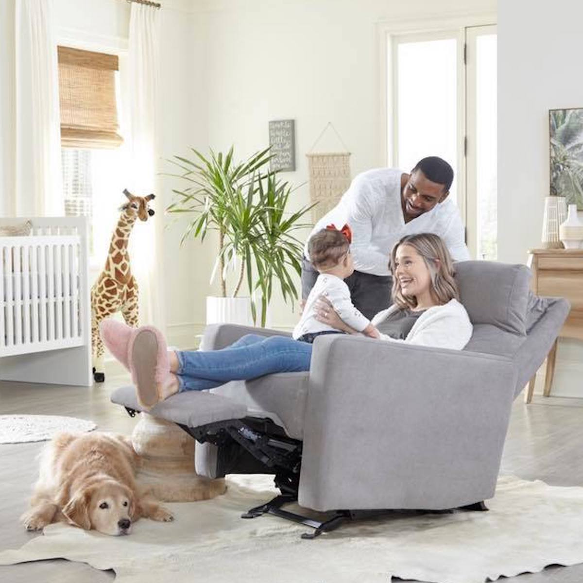 Two parents and their toddler sitting on a grey Nurture& glider with their golden retriever on the floor