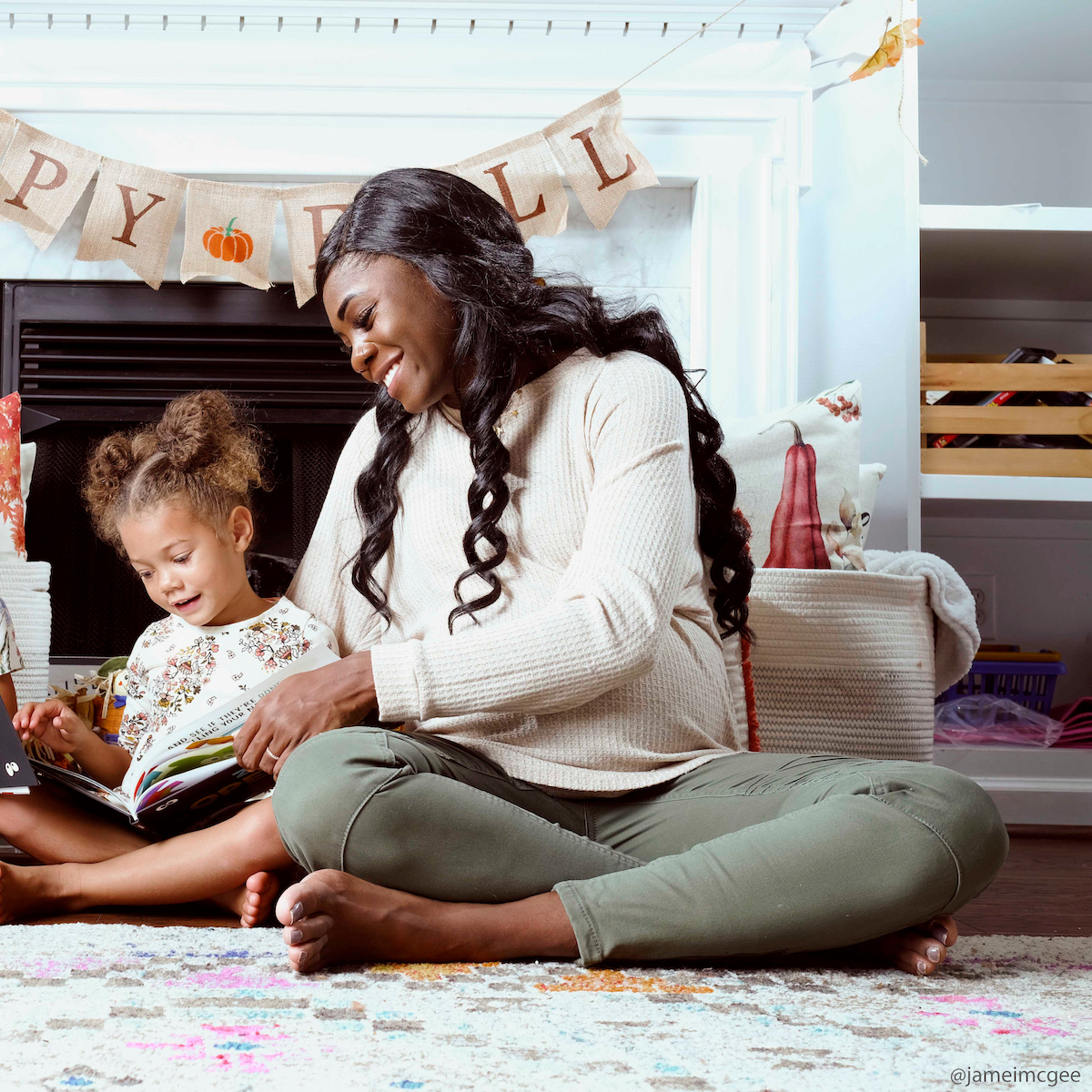 A mother reading an I See Me! Book on the floor of their living room.