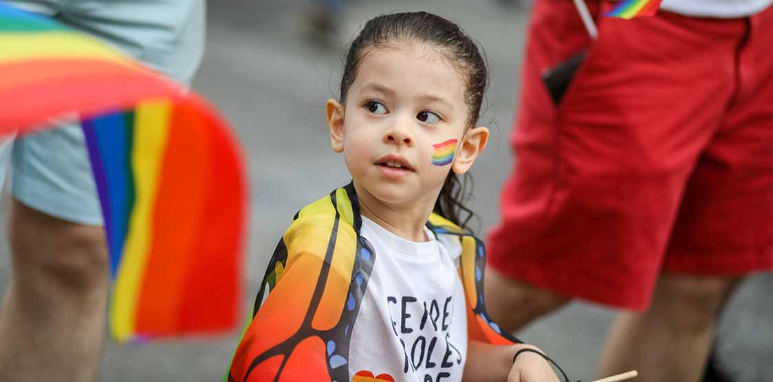 Young girl draped with a rainbow flag
