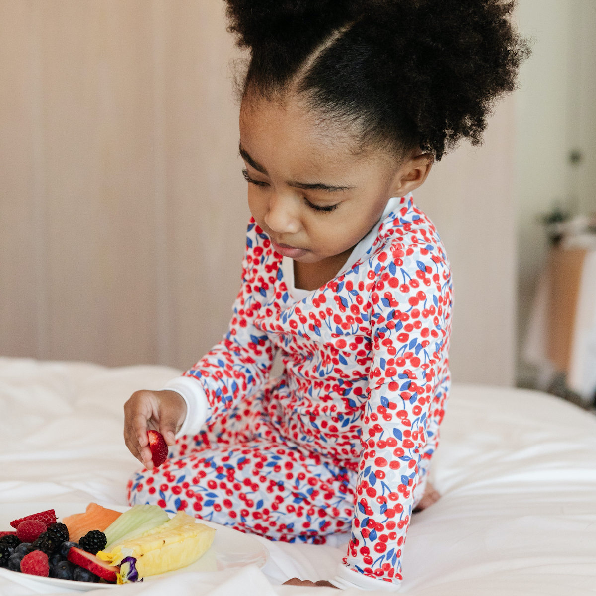 A little girl wearing 12 | 12 pajama set and eating a plate of fruit on a bed.