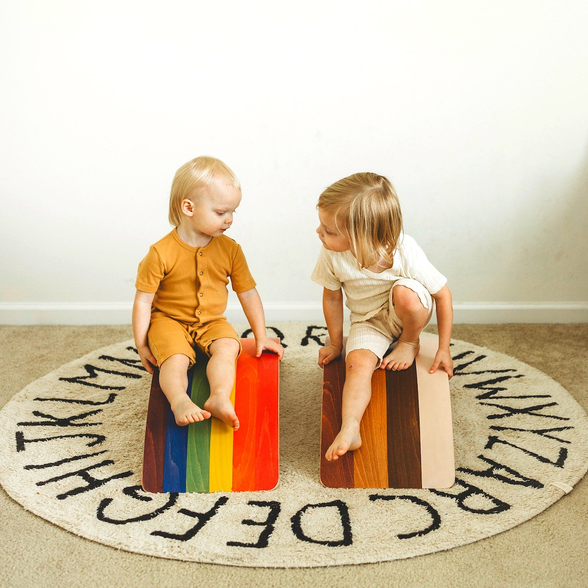 Two toddlers sitting on a Rainbow Bunny Hopkins Wobble Board on top of an alphabet play mat