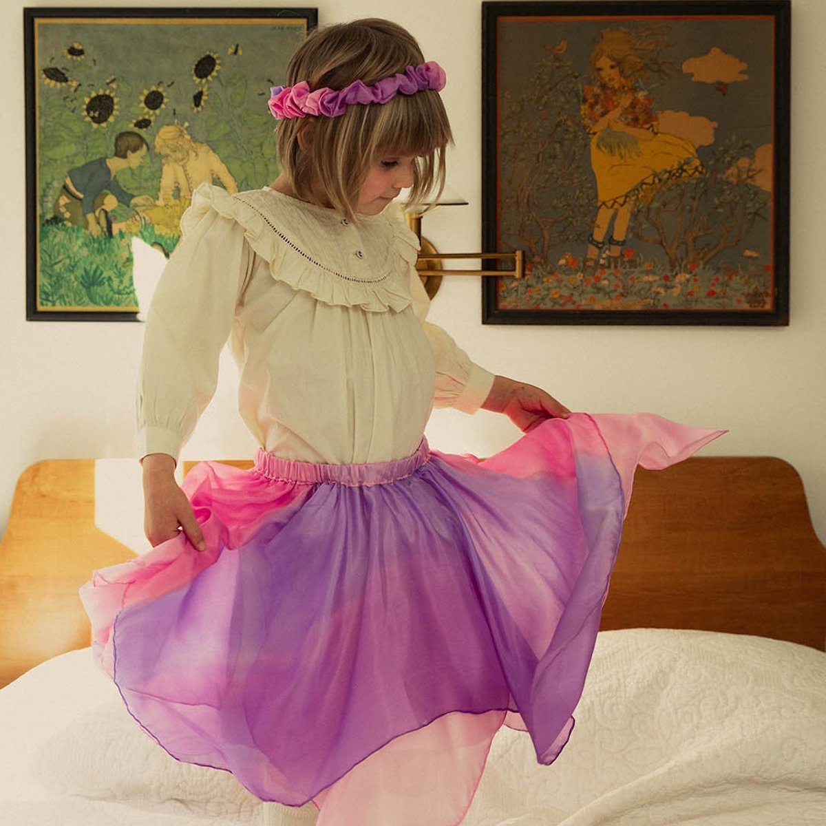 A little girl jumping on a bed wearing a Sarah's Silks pink skirt and flower crown