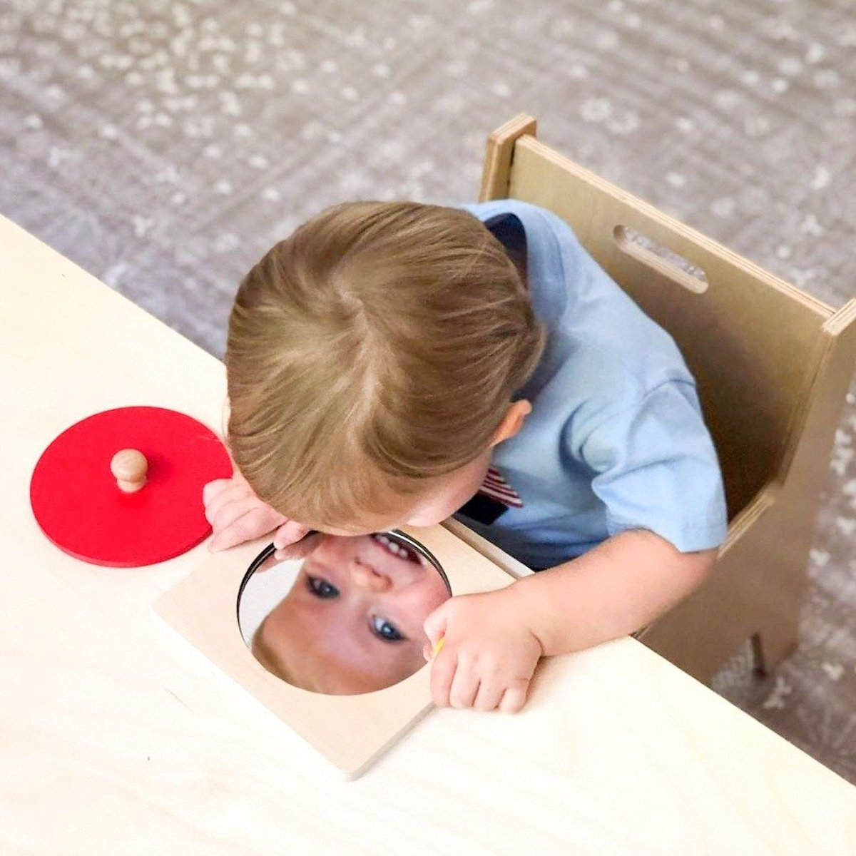 A toddler sitting at a wooden desk and looking down at a Familiar Faces Mirror puzzle